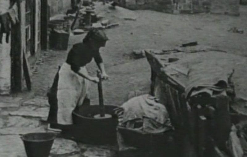 """Mujer lavando con un """"washing dolly"""""""